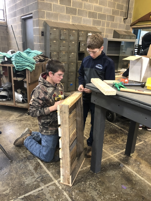 David S and Drake S work on a project built out pallets in class.